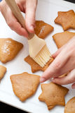 Decorating gingerbread. A chef decorating gingerbread cookies, basting them with syrup Royalty Free Stock Photo