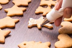 Decorating of gingerbread bears on wooden table Royalty Free Stock Image