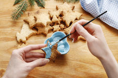 Decorating gingerbread cookies with blue and white icing. Stock Photography