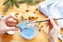 Decorating gingerbread cookies with blue and white icing. Stock Images