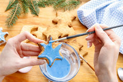 Decorating gingerbread cookies with blue and white icing. Royalty Free Stock Photos