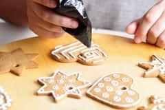 Decorating gingerbread cookies. Stock Photos