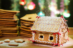 Decorating gingerbread cottage with icing sugar Royalty Free Stock Photos