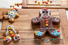 Decorating gingerbread man for Christmas on wooden table Stock Photography