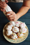 Decorating muffins with butter-cream Royalty Free Stock Photos