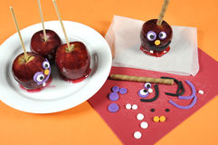 Decorating red toffee apples with funny crazy smiling faces for Halloween. Trick or treat food candy, on an orange table setting Stock Photography