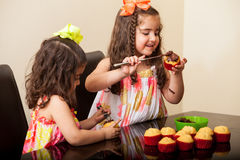 Decorating some cupcakes. Cute brunette and her sister decorating some cupcakes with chocolate at home royalty free stock photos