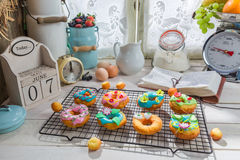 Decorating sweet donuts in the rustic kitchen. On old wooden table stock image