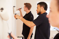 Decorating team painting a room in a house Stock Photos