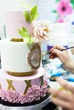 Decorating tiered mastic weeding cake with flowers and colouring details by brush stock image