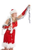 Decorating the tree. Pretty young girl in santa dress hanging up the baubles Stock Images