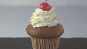 Decorating vanilla cupcake. Decorating vanilla cupcake with whipped cream and cherry. Close up stock footage