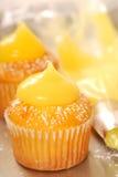 Decorating vanilla cupcakes royalty free stock photography