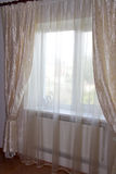 Decorating windows - cream curtains in the bedroom Stock Photo