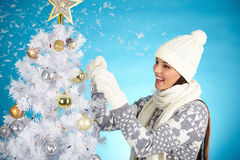 Decorating xmas tree. Young woman in white knitted winterwear decorating Christmas tree stock images
