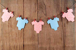 Decoration for Baby shower on wood desk. Color garland from infant shirt. Gift box Stock Photo