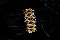 Decoration bracelet jewelry gold plastic blue. On a black background Royalty Free Stock Photo