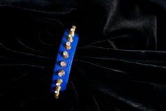 Decoration bracelet jewelry plastic blue gold. Rhinestone studs on a black background Royalty Free Stock Photos