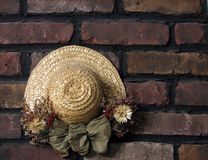 Decoration on Brick Wall. Shot of a spring/summer hat decorated with dried flowers, hanging on a brick wall royalty free stock images