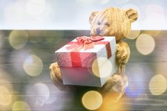 Teddy bear hold gift with bokeh. Decoration of brown teddy bear hold gift box on black textured wood and light bokeh with copy space for text.  Valentines day Stock Photography