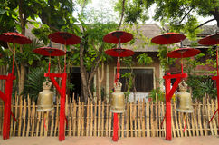 Decoration at the Buddhist temple: bells under red umbrellas Royalty Free Stock Images