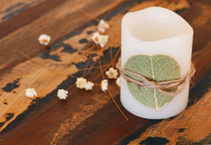 Decoration candle with dried leaf ando flowers on wooden table Royalty Free Stock Image