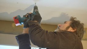 Decoration of the ceiling. The worker screws the sheet of plasterboard to the ceiling with an electric screwdriver. stock video