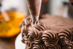 Decoration of chocolate cake with culinary syringe. Closeup view. Homemade dessert stock photo