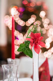 Decoration on christmas decoration. Red candles and red flower on christmas table. Bokeh, blur background Stock Photography