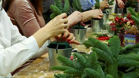 Decoration of Christmas gift bouquets. Women`s hands collect a bouquet. Handmade production of small decorated Christmas trees stock video