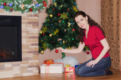 Decoration of Christmas tree. Beautiful young woman decorates a Christmas tree at home Royalty Free Stock Images
