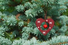 Christmas decoration. Decoration on christmas tree red heart with bell hanging on green blue tree branch with copy space for text. Christmas spirit and Stock Photo
