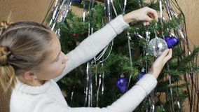 Decoration of a Christmas tree. A teenage girl decorating a Christmas tree with Christmas toys stock footage