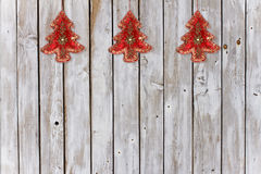 Decoration with Christmas Tree Velvet Ornaments on Weathered Natural Background. Series of three velvet sequined Christmas tree ornaments on wheatered wooden stock photography