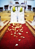 Decoration church to wedding ceremony, petals on a red carpet.  Royalty Free Stock Photo