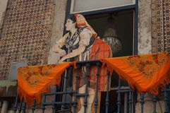 Decoration in the city of Lisbon - Front view. Decoration in the city of Lisbon. Region of Alentejo. A Portuguese woman in the balcony with an orange scarf on Stock Photos