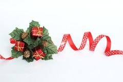 Decoration of crown-shaped parties on white background with red ribbon, green leaves and red gifts Stock Photos
