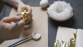 Decoration of Easter eggs with gold foil.  stock video