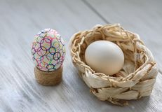 Decoration for Easter. One Easter egg Colored drawings and one egg in a wicker basket on a wooden table stock photography