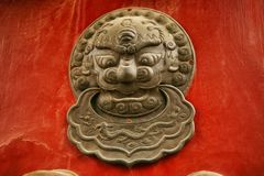 The decoration element of a red wooden door in the form of a lion`s head in the Forbidden City, Beijing, China royalty free stock photography