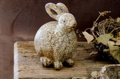 Decoration with flowers, and a funny,fatty,rabbit. On textured old table Stock Images