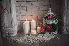 Decoration of fretwork fireplace with flowers, candles and bead.  Royalty Free Stock Photo