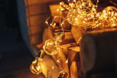 Decoration gerland christmas lights bulb lying in fireplace on wooden firewood loft design. Fireplace of whote brick royalty free stock photos