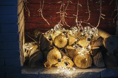 Decoration gerland christmas lights bulb lying in fireplace on wooden firewood loft design. Fireplace of whote brick stock image