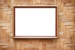 Decoration gold picture frame hanging on wood woven wall background royalty free stock photo