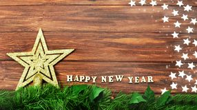 Decoration gold star on a Christmas tree on a wooden background. With the text of a happy new year 2018 and stars shining Royalty Free Stock Photography