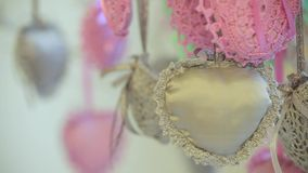 Decoration hearts are hanging from tree. Dynamic change of focus. Close up. Decoration pink and grey hearts are hanging from tree, knitted hearts grey and rose stock video footage