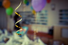 Decoration for the holiday, tape from the balloon. Decoration for holiday with blurred background golden ribbon with balloon Royalty Free Stock Photo