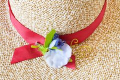 Decoration of ladies` straw hat close up. Decoration of ladies` straw hat with red band and textile flower close up Royalty Free Stock Photos