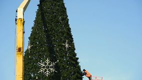 Decoration of a large urban Christmas tree. Workers on the crane install and decorate the Christmas tree stock video footage